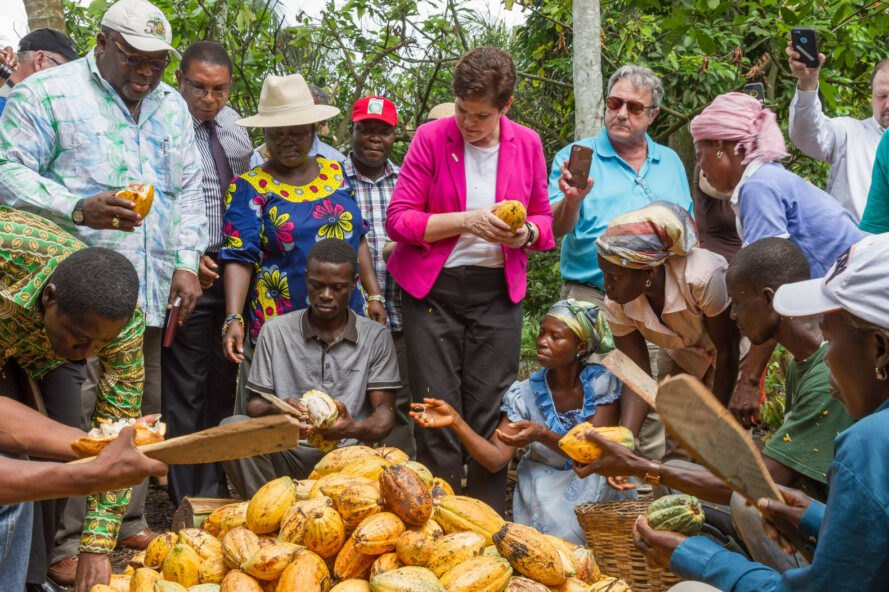 Ghana Agriculture Deputy Secretary Krysta Harden examines cocoa pods alongside rural workers