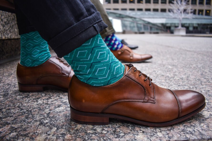 man in suits wears turquoise socks