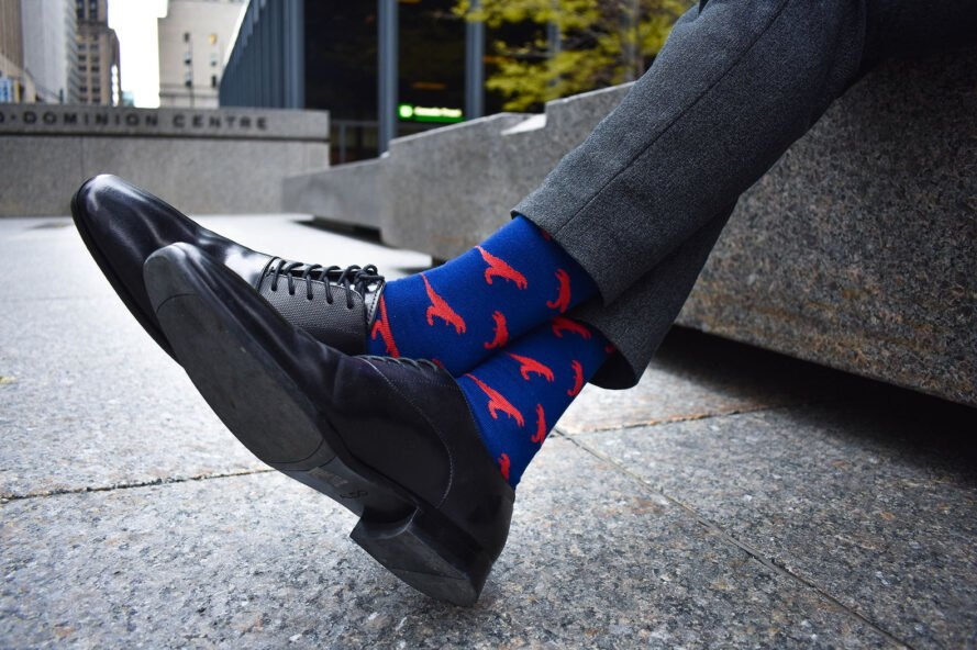 man in suit wears blue socks with red dinosaurs