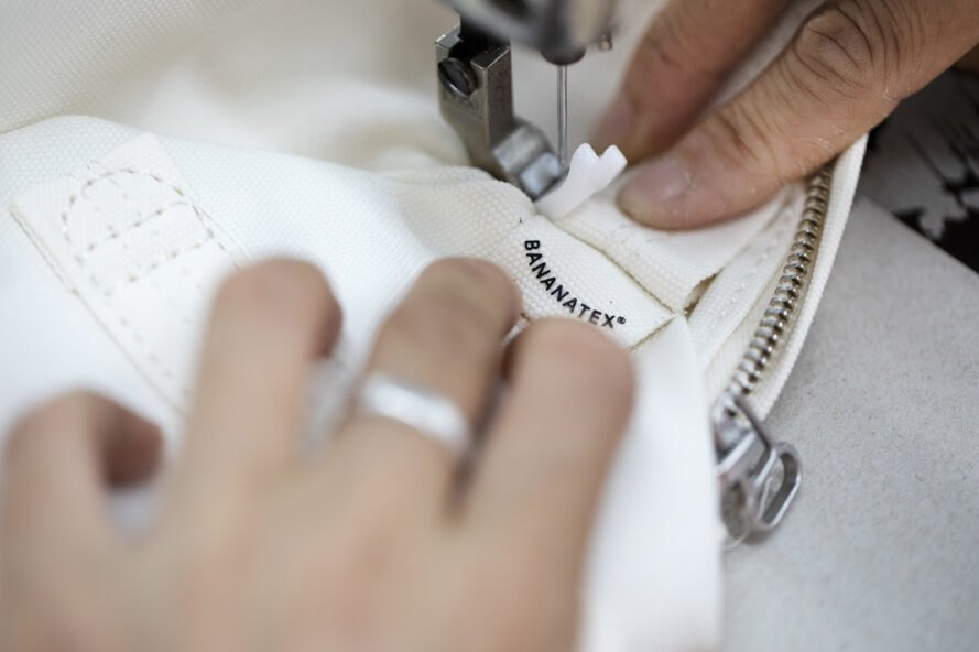 person sewing a tag onto a white bag