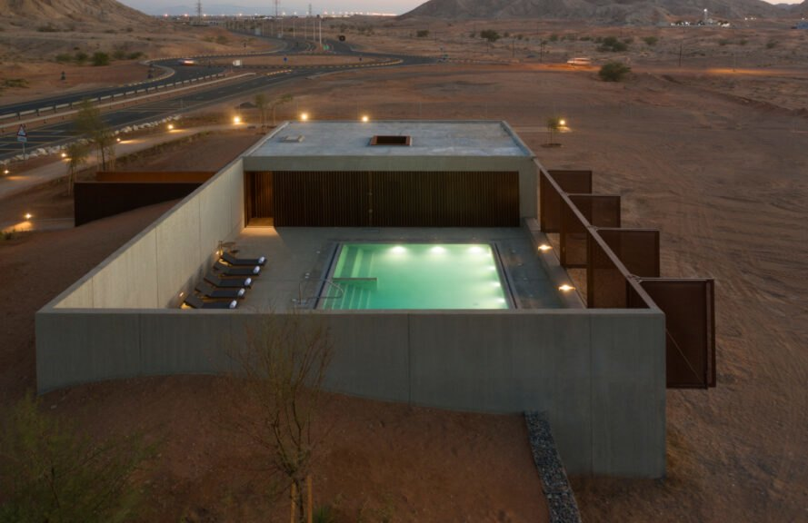 single-story building with a pool in a desert landscape