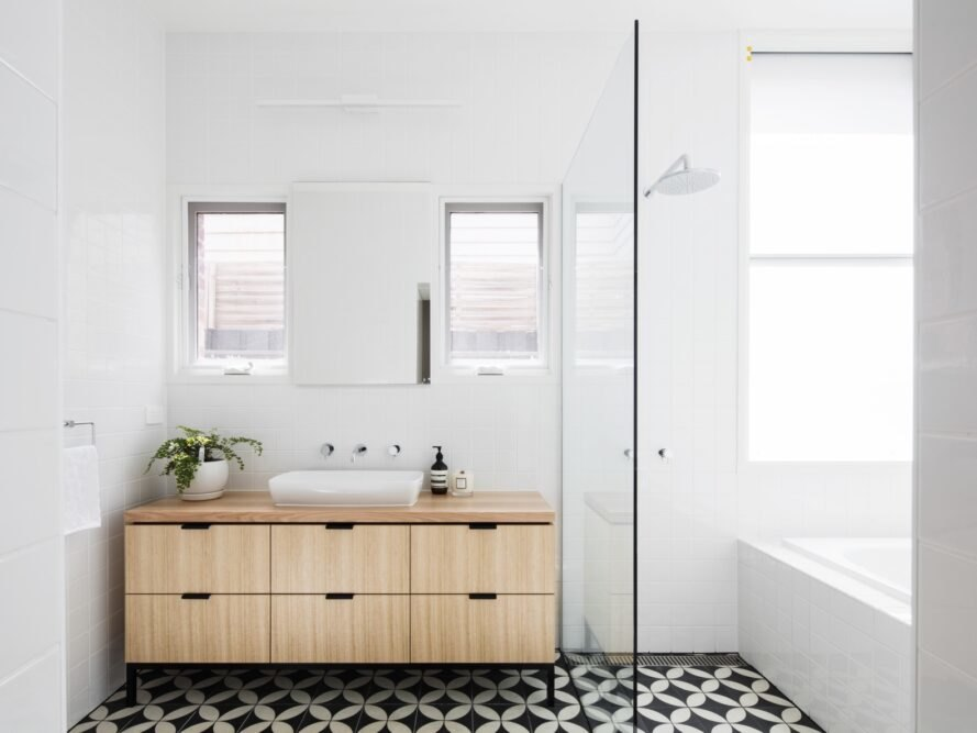 black and white tiles lines the bathroom floor with white walls and a wood sink countertop