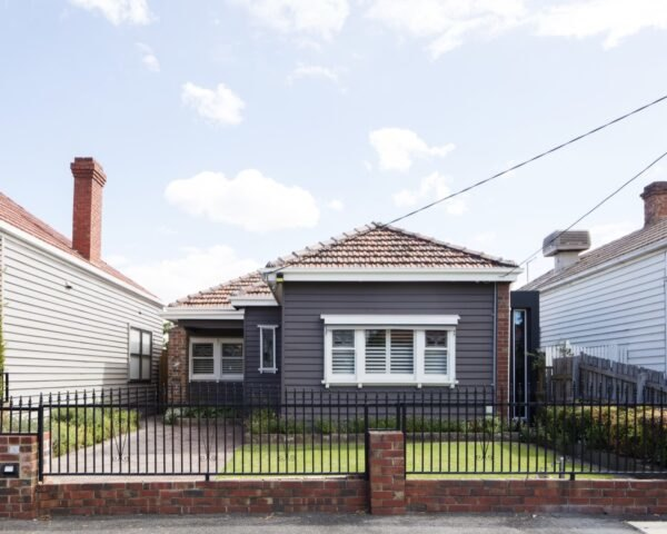 small gray cottage home with front yard
