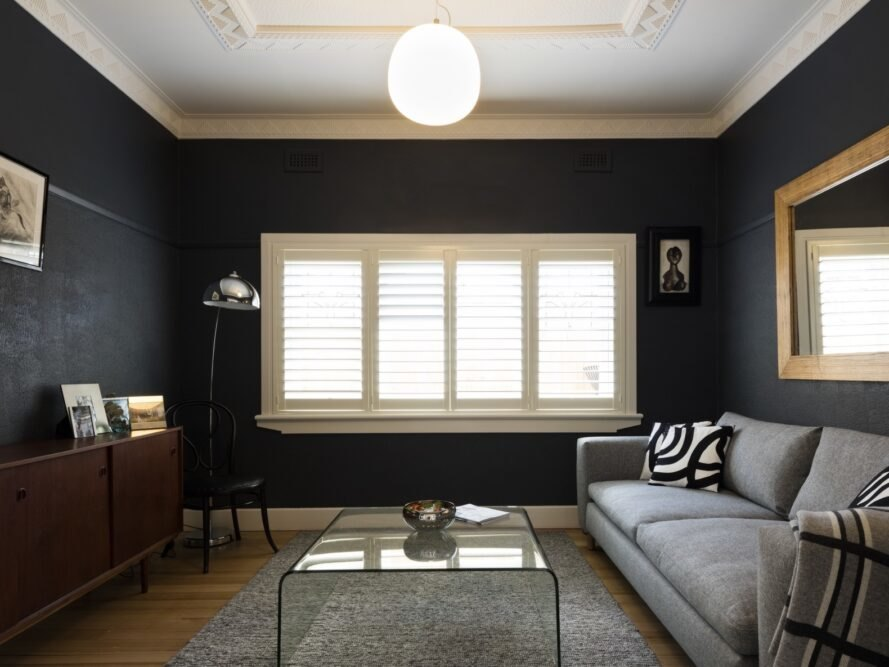 a gray couch is placed next to a black wall with white and brown framed windows with wood floors
