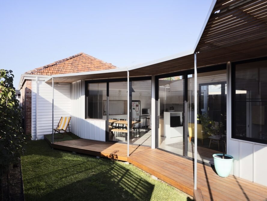 white walls of the home with black borders and an outdoor hardwood walkway under a terrace