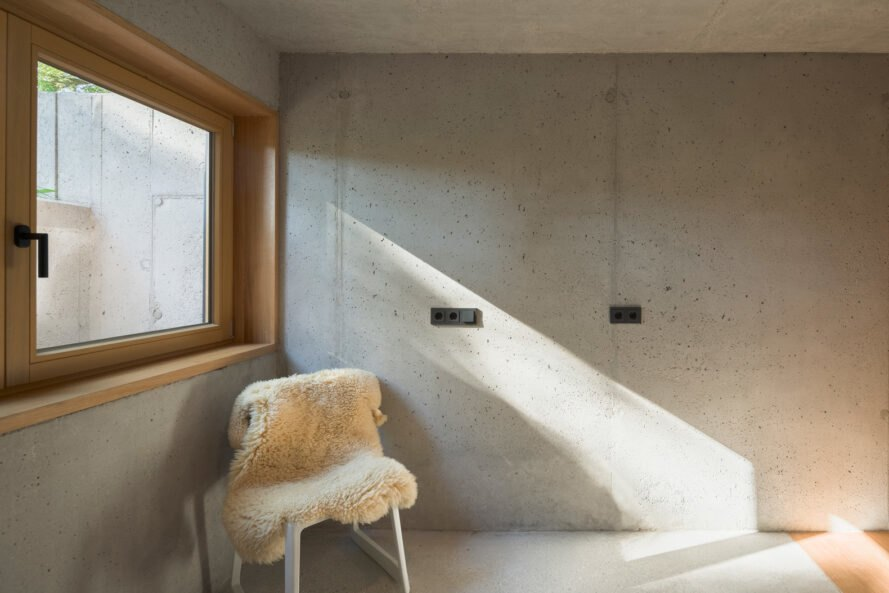 white chair with white fur is placed next to a wide window with wood frame and concrete walls