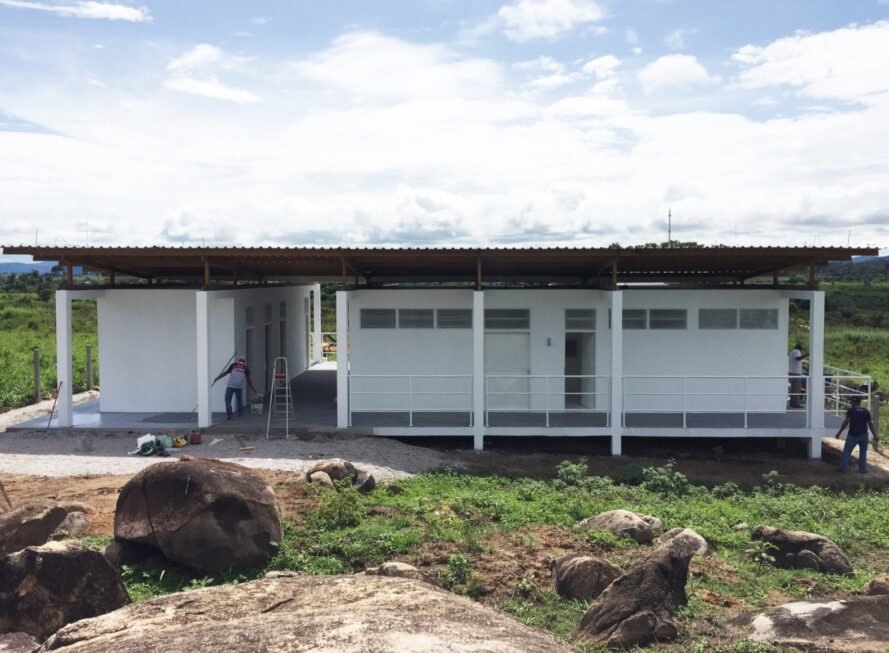 white beekeepers workshop surrounded by grass