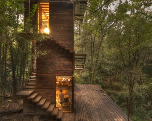 wood treehouse with wood spiraled stairs surrounded by forest with interior lights illuminating the home
