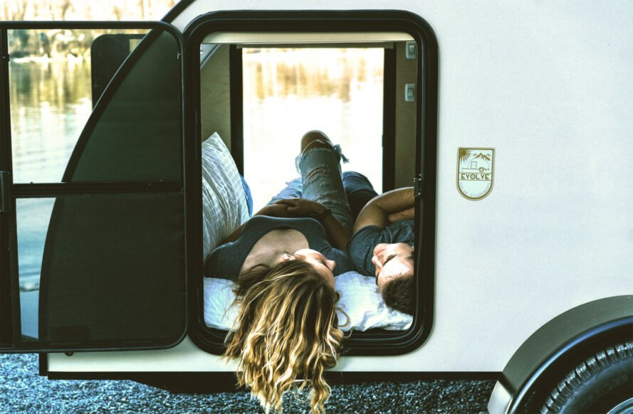 two people lying down inside teardrop trailer