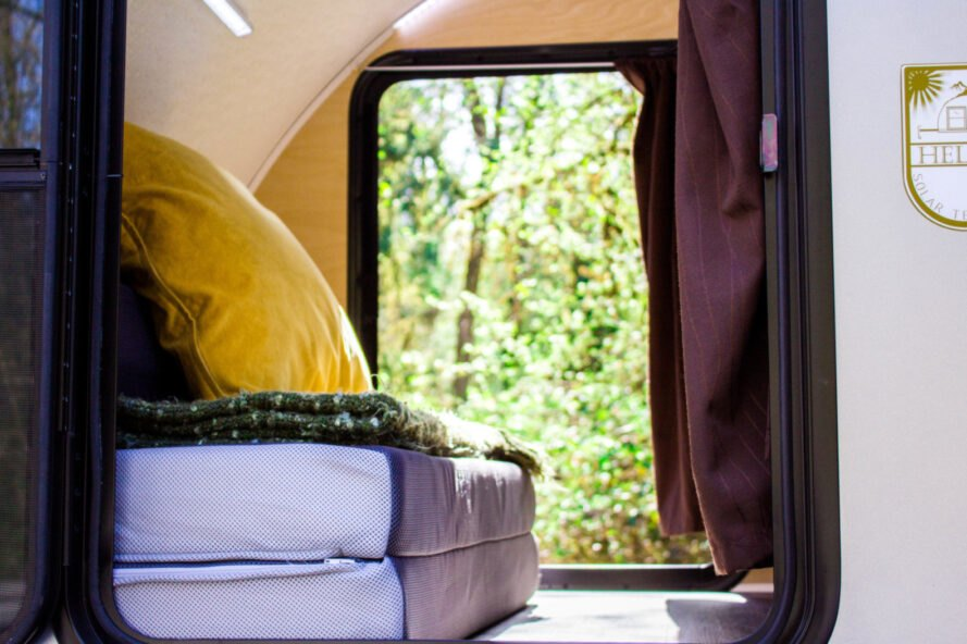 bed facing a window inside a teardrop trailer