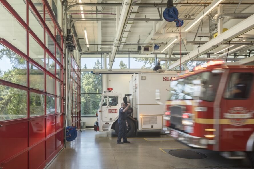 interior of fire station garage with fire trucks and fire fighter