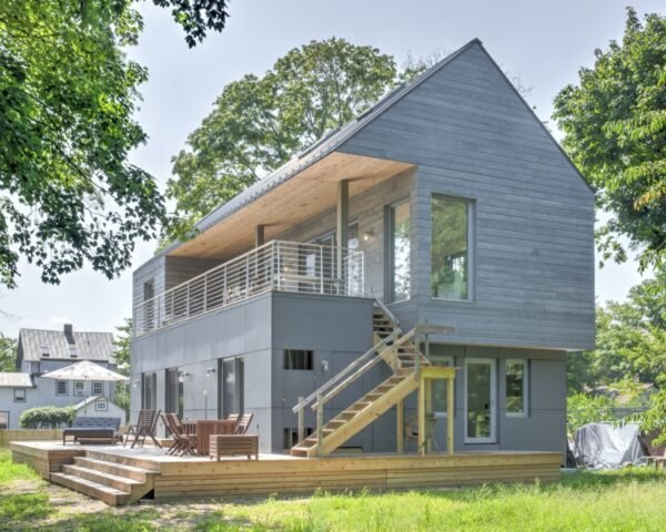 home with gray cedar siding and second-story deck