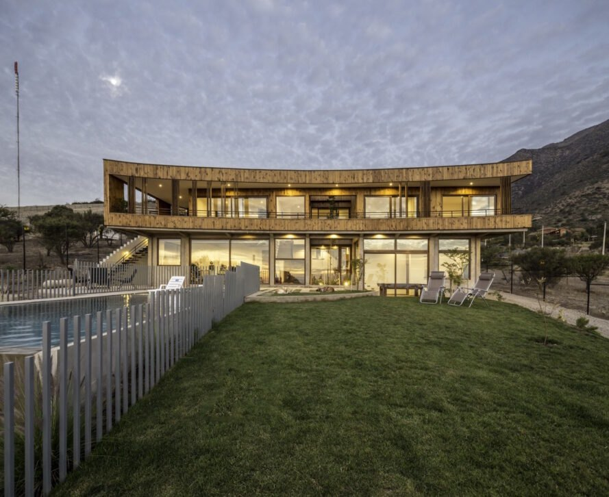 grassy lot in front of curved wooden home