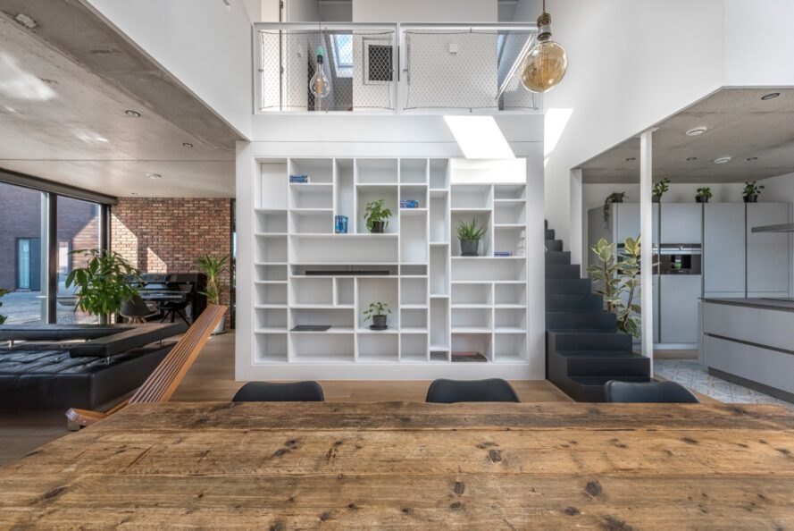 wooden floors in lower level of the home with nearby staircase and white bookshelf