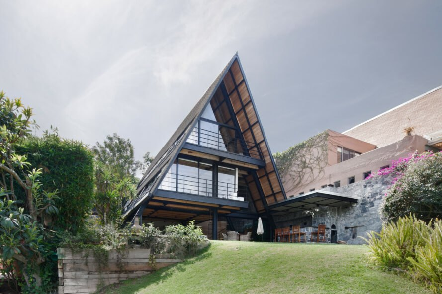 black A-frame home with glass walls