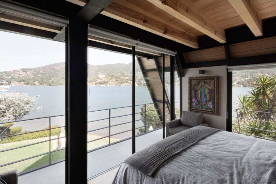 bedroom with glass walls revealing lakeside views