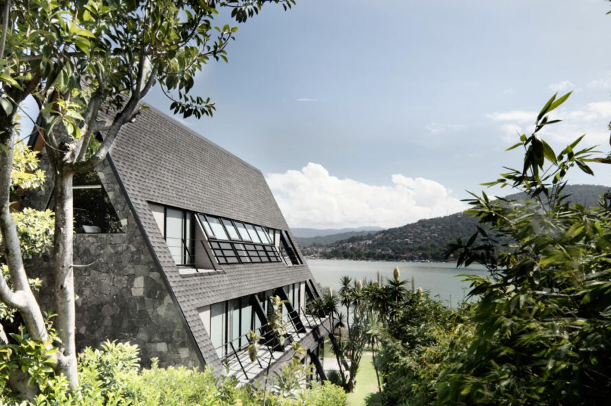 side of A-frame home and views of a lake