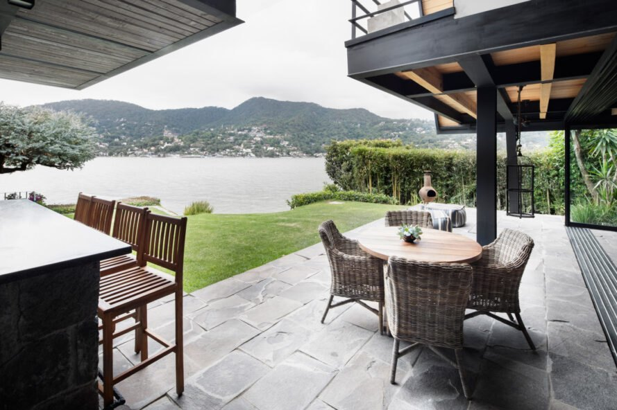 outdoor bar with stools and dining table with views of the lake