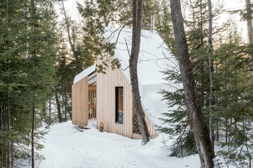 wood cabin with sloped roof covered in snow
