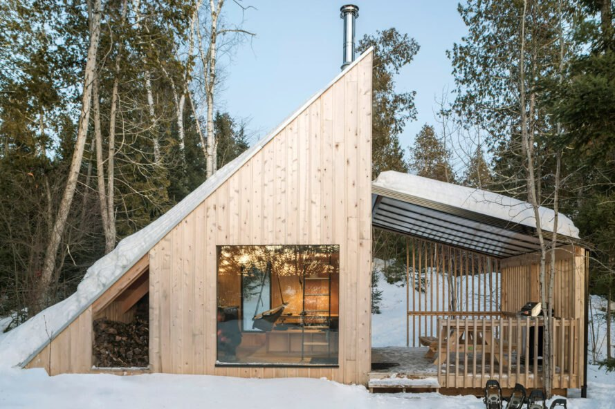 wood micro home with sloped roof in wintery forest