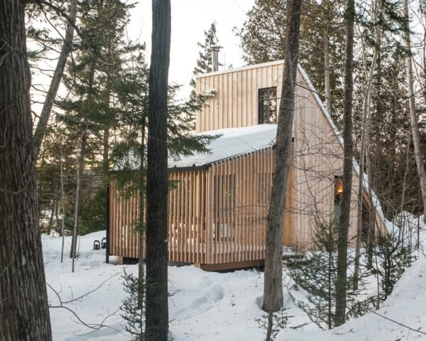 wood A-frame micro home in snowy forest