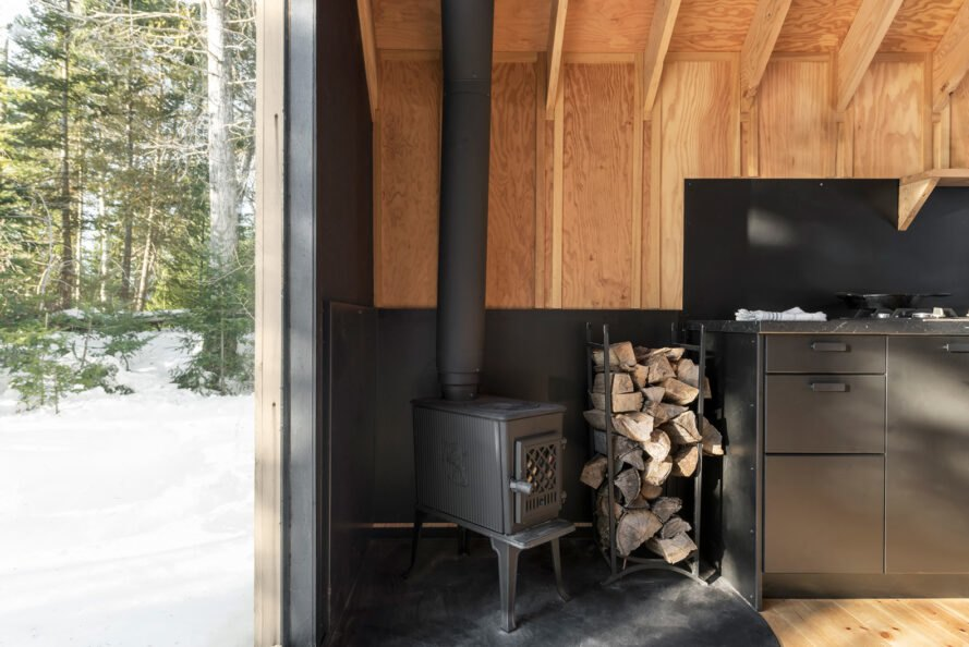 black wood-burning stove with stack of firewood next to it