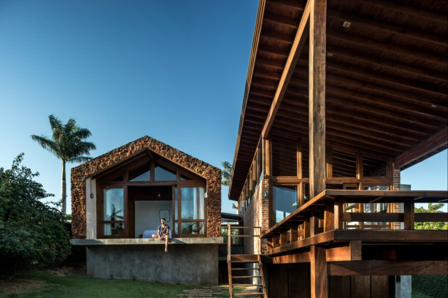 stone home with pitched roof and wooden deck