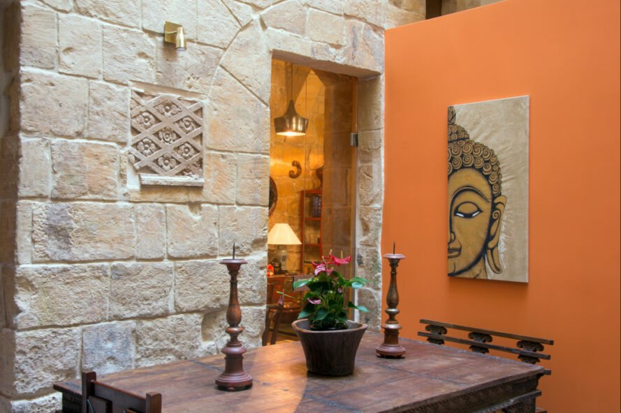 room with stone walls and Buddha art