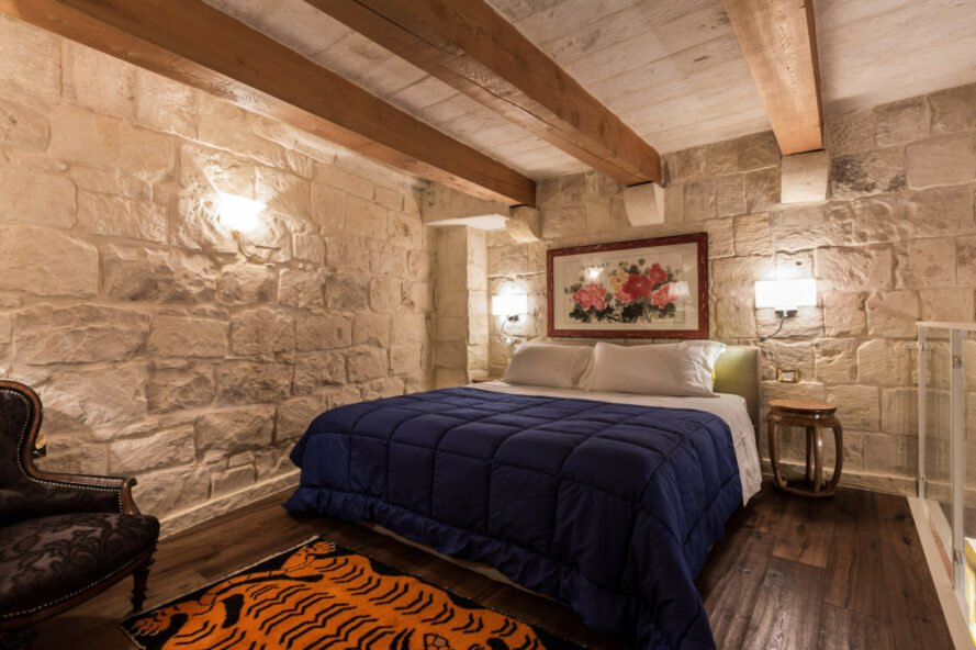 guest room with large bed, stone walls and wood ceiling beams