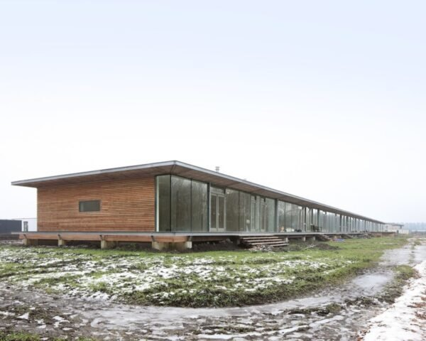 long wood building raised from the ground in a large open land with grass and snow
