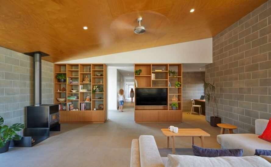 living area with plywood ceiling and bookshelves