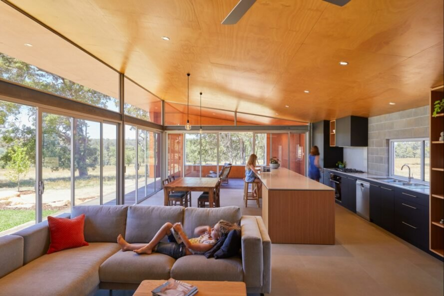 large living area with plywood ceiling and glass wall