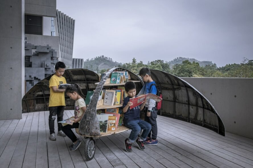 children checking out books from a metal contraption on wheels in the shape of a beetle