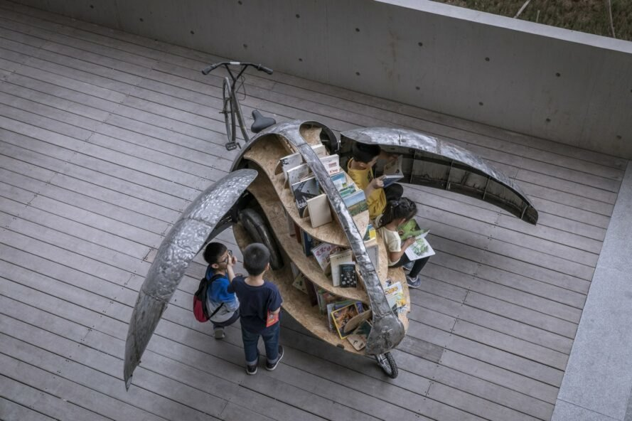 kids reading books from a small library cart