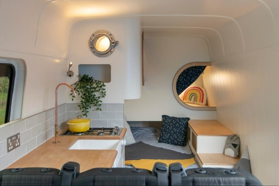 camper van interior with tiny kitchen and a day bed