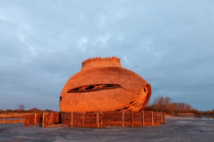 oval wooden bird observatory lit up at dusk