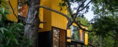 elevated vibrant yellow prefab home surrounded by greenery