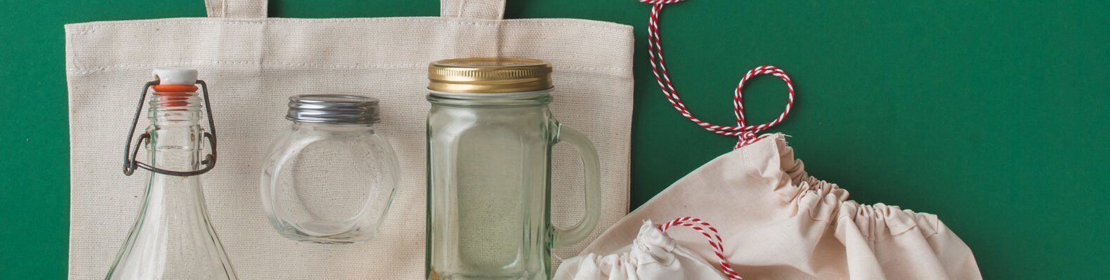 glass jars and cloth bags on green background