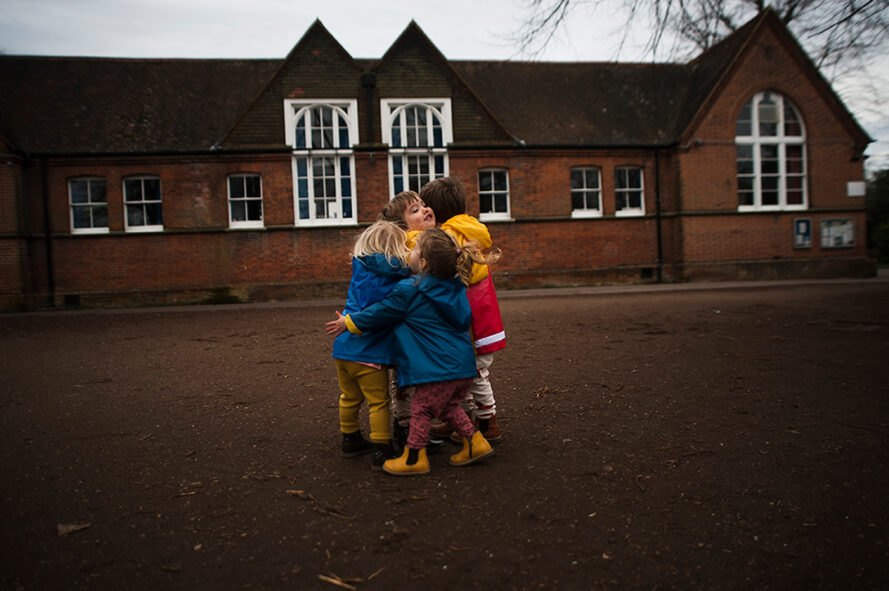 group of kids in raincoats hugging
