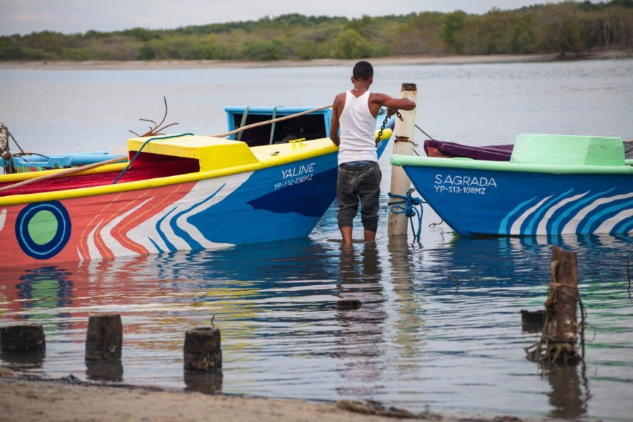person docking a couple of colorful boats