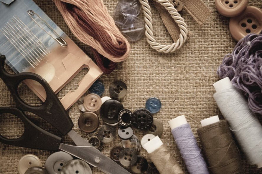 contents of a sewing kit displayed on burlap background
