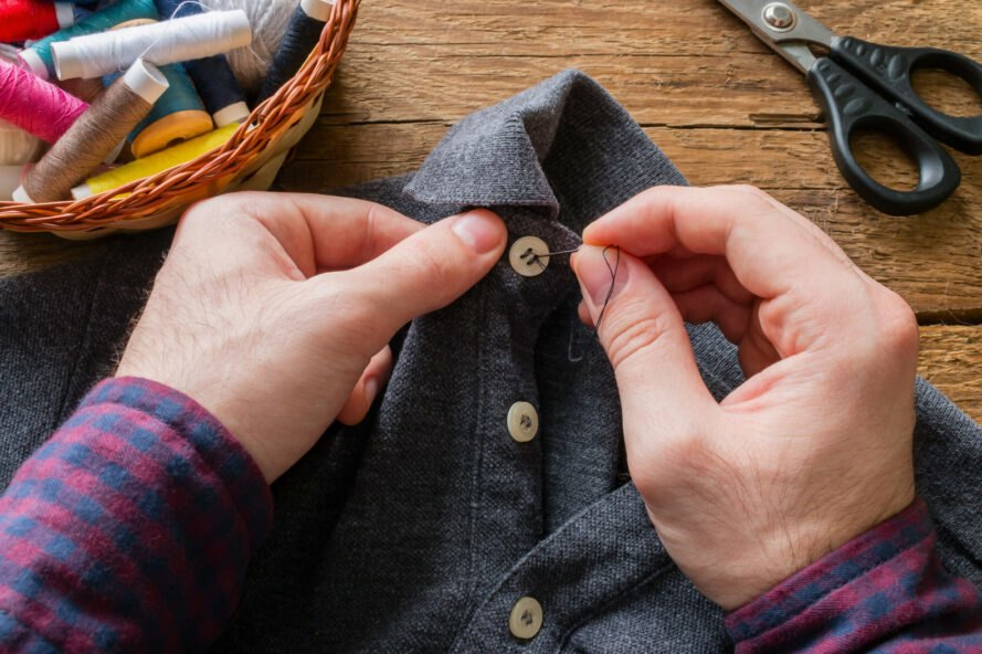 person sewing button on a shirt