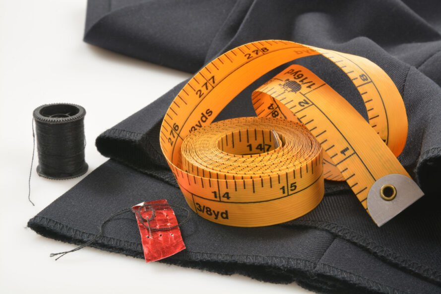 measuring tape and thread on top of pants that need hemmed