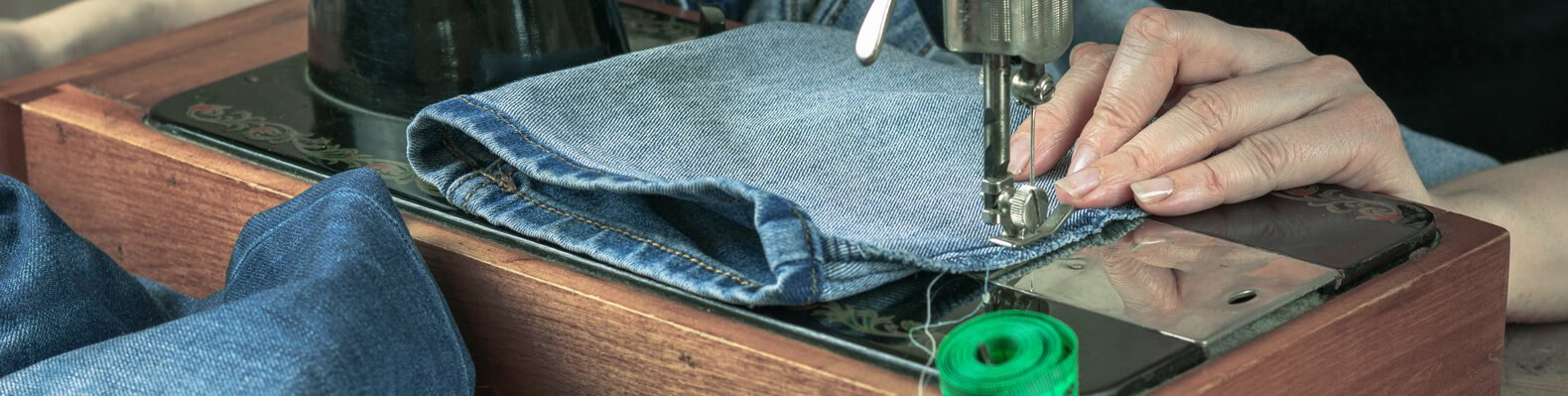 person sewing denim pants on a sewing machine