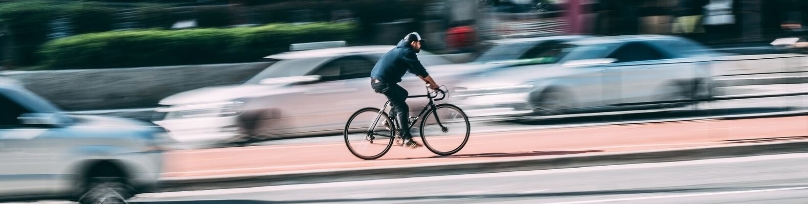 person riding bike as cars drive past