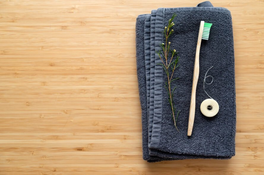 bamboo toothbrush and natural floss on blue washcloth