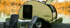 yellow teardrop camper with back hatch open and two seats out front
