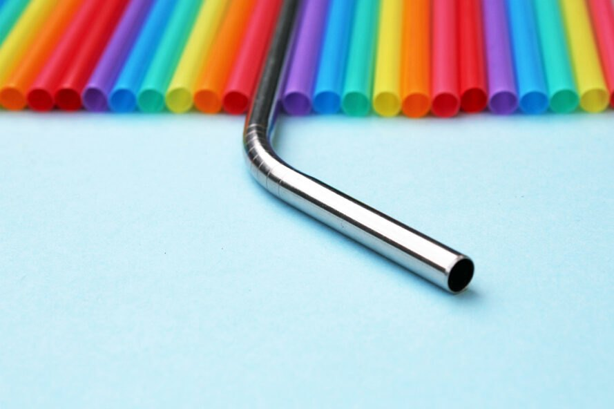 rainbow colored plastic straws with reusable metal straw between them