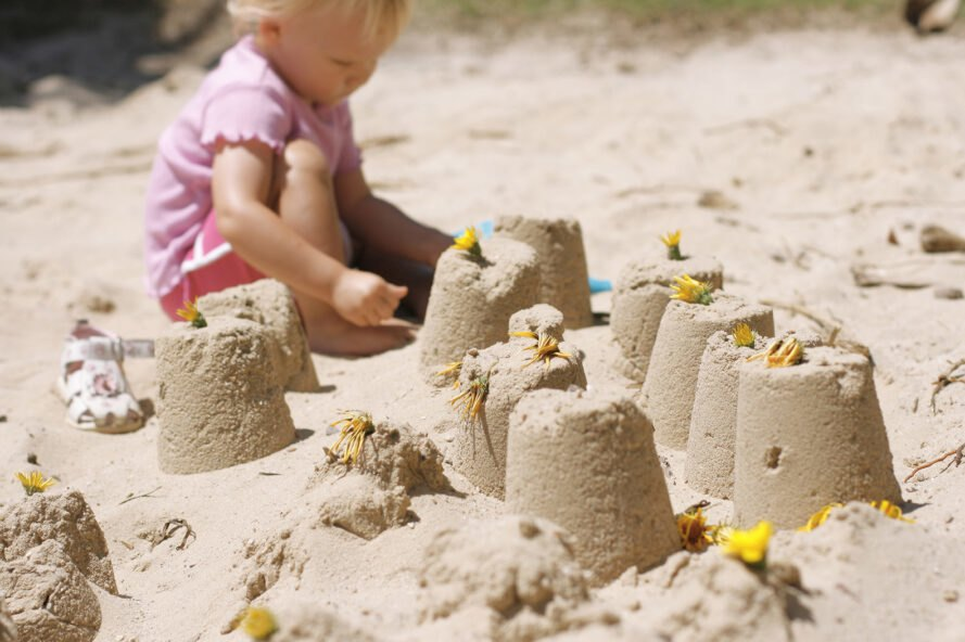small girl builds sandcastle