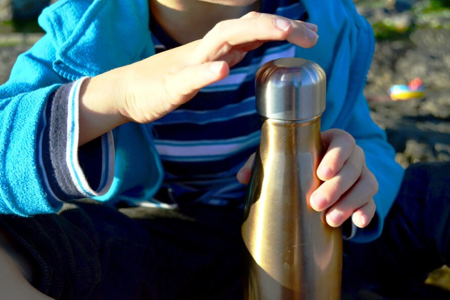 child's hands holding a reusable metal water bottle